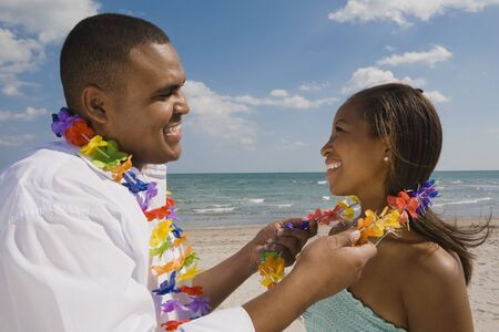 vacationing: African couple wearing leis