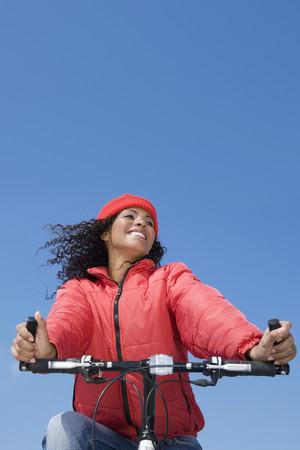 Hispanic woman riding bicycle Stock Photo