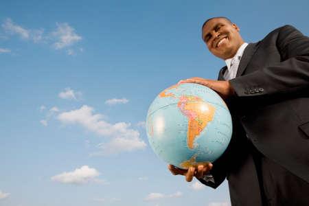 holding globe: African businessman holding globe