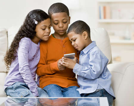 playing on divan: Mixed Race siblings looking at hand-held game