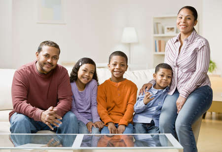 family sofa: Mixed Race family sitting on sofa