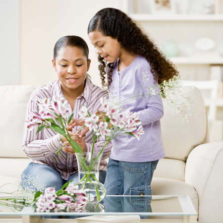 bathtowel: Mixed Race mother and daughter arranging flowers