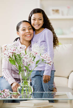 Mixed Race mother and daughter hugging Stock Photo