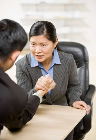 adventuresome: Asian businesspeople arm wrestling