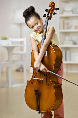 playing on divan: Mixed Race girl holding cello