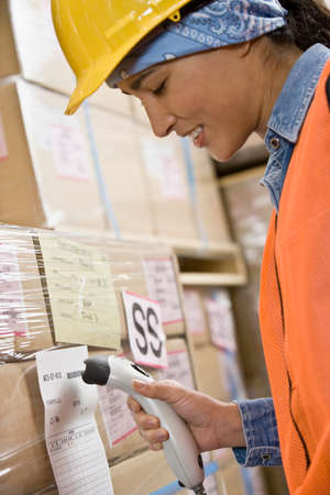 cardboard only: Hispanic warehouse worker scanning shipment