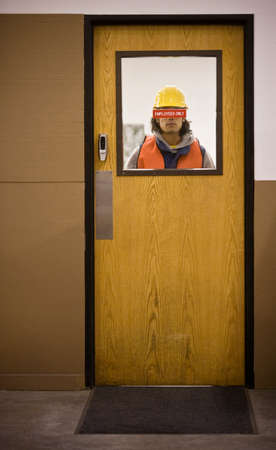 negative area: Asian warehouse worker looking through door LANG_EVOIMAGES