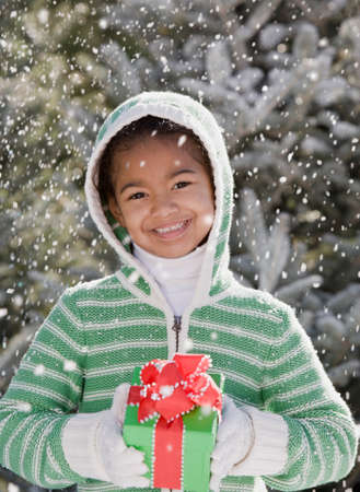 gusto: African girl holding gift in snow