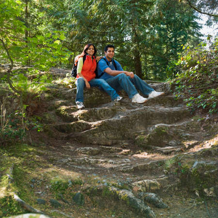 intersecting: Indian couple sitting in woods LANG_EVOIMAGES