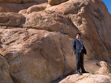 African businessman standing on rock