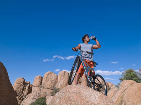 milepost: African man with mountain bike on rocks LANG_EVOIMAGES