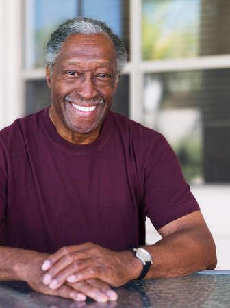 receding: Senior African man sitting at outdoor table