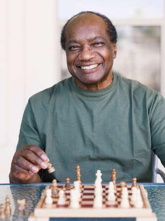 chess men: Senior African man playing chess LANG_EVOIMAGES