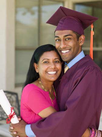one parent: Indian mother hugging graduate son LANG_EVOIMAGES
