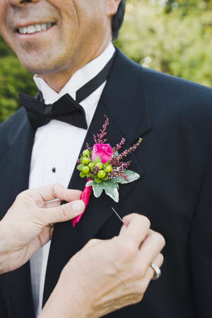 pinning: Asian woman pinning groom's boutonniere