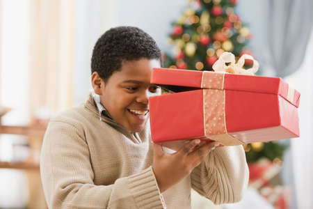 eagerness: African boy peeking into gift LANG_EVOIMAGES