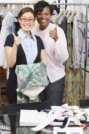 Multi-ethnic fashion designers giving thumbs up Stock Photo