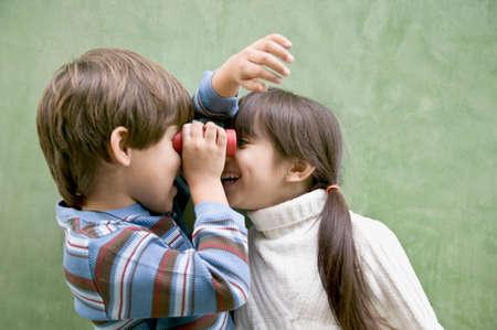 bathingsuit: Hispanic siblings looking at each other through binoculars