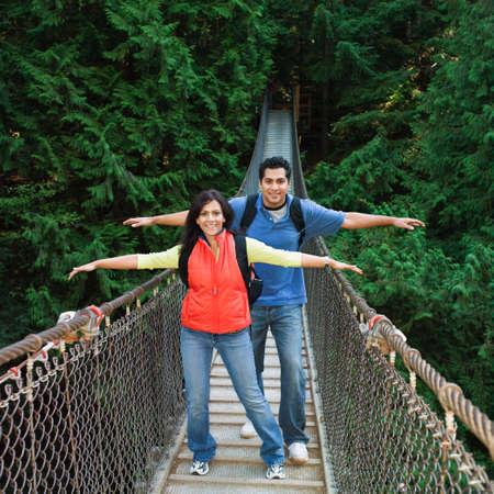 ceasing: Indian couple wearing backpacks on footbridge