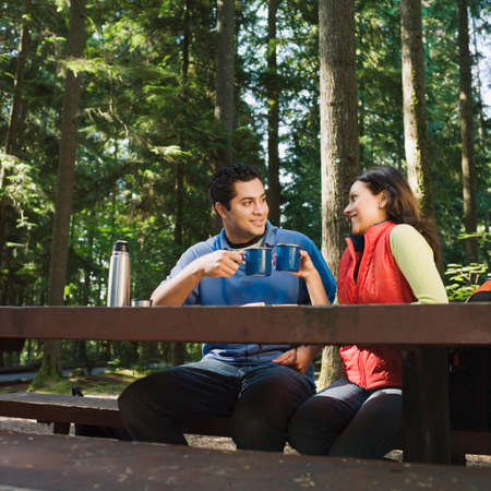 adventuresome: Indian couple drinking coffee in woods LANG_EVOIMAGES