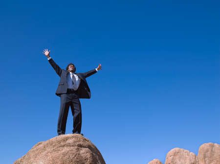 spectating: African businessman standing on top of rock LANG_EVOIMAGES