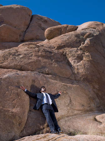 rockclimber: African businessman leaning on rock