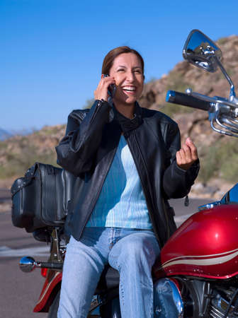 adventuresome: Hispanic woman on motorcycle talking on cell phone