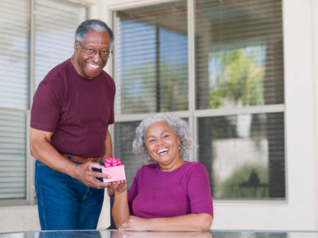 50s man: Senior African man giving gift to wife