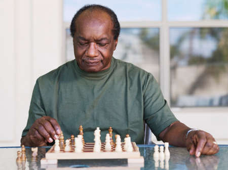 bestowing: Senior African man playing chess LANG_EVOIMAGES