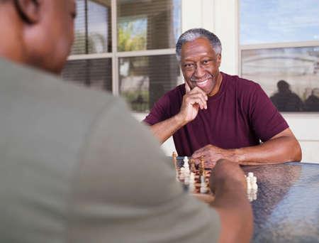 black: Senior African man playing chess LANG_EVOIMAGES