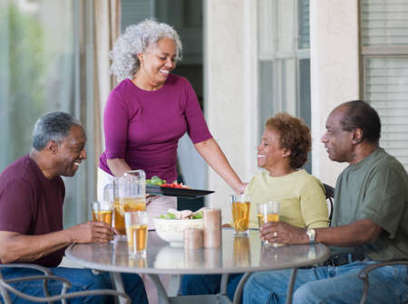 relishing: Senior African couples eating on patio