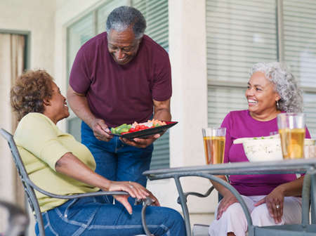 old furniture: Senior African couples eating on patio