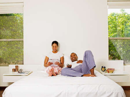 slumbering: African couple relaxing in bed LANG_EVOIMAGES