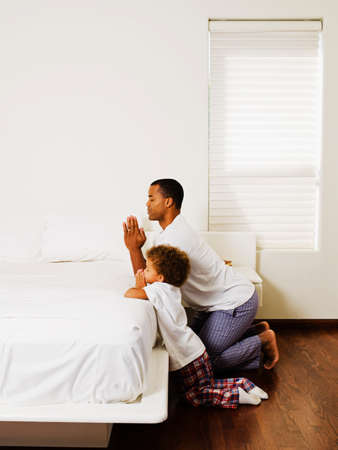 African father and son praying at bedside Stock Photo