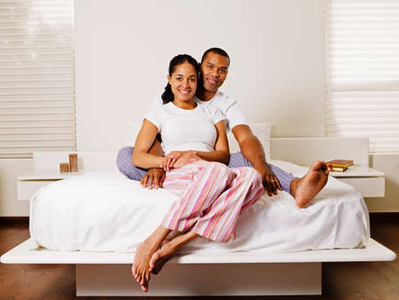 pjs: African couple sitting on bed