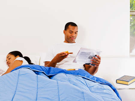 African man reading next to sleeping wife Stock Photo