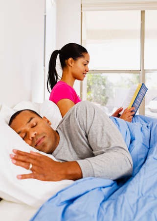 rousing: African woman reading next to sleeping husband LANG_EVOIMAGES