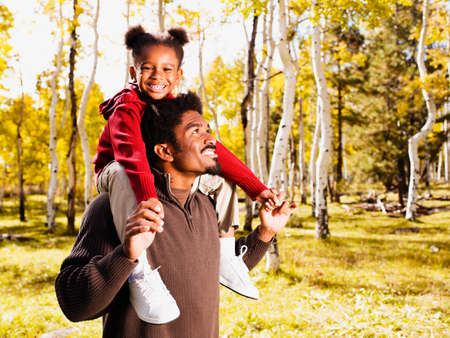 father daughter: African father holding daughter on shoulders
