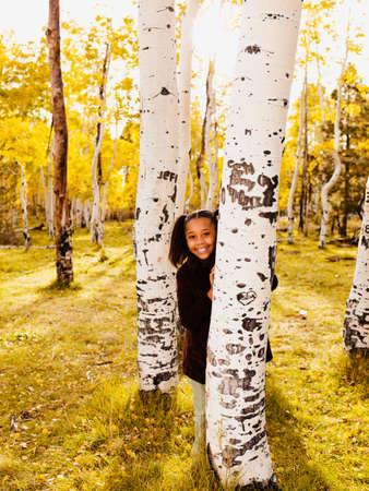 adventuresome: African girl standing behind tree