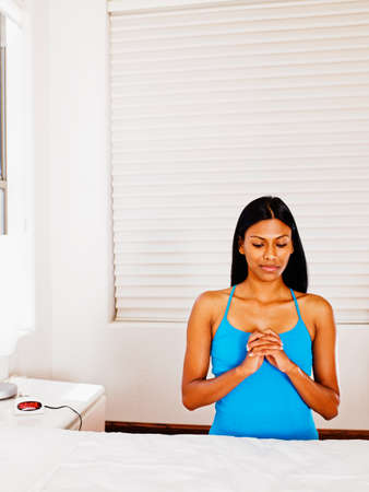 bedside: Indian woman praying at bedside