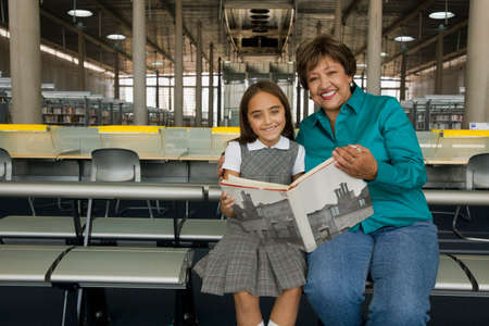 prevailing: Hispanic grandmother and granddaughter reading library book