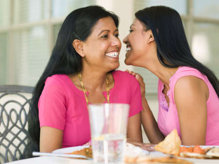 blabbing: Indian woman telling secret to mother LANG_EVOIMAGES