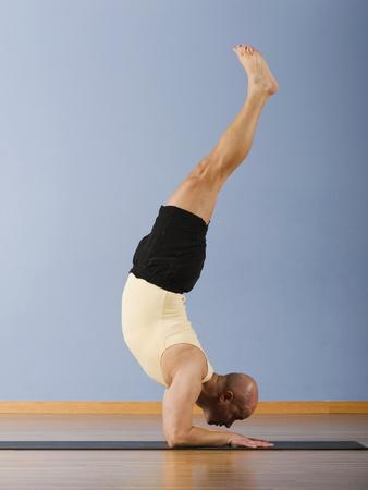 squatter: Hispanic man practicing yoga