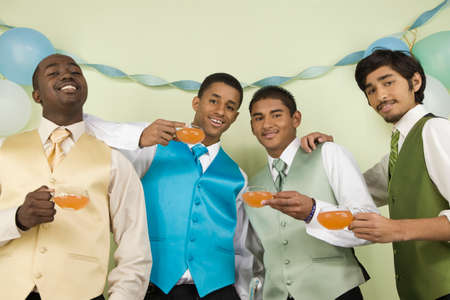 milepost: Multi-ethnic men in suits holding cups of punch LANG_EVOIMAGES