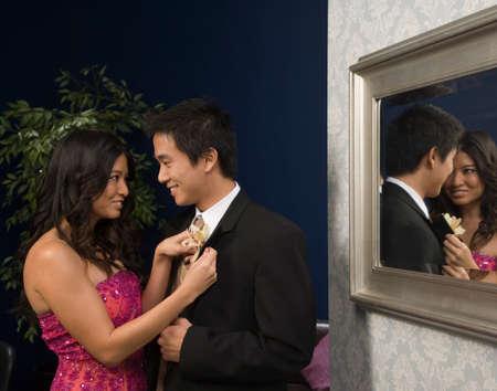 milepost: Asian woman fastening boyfriend's boutonniere LANG_EVOIMAGES