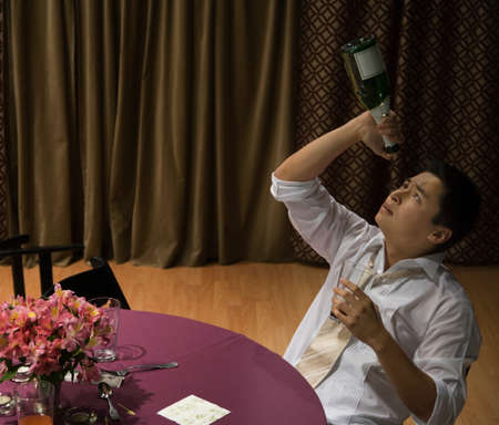 ostentatious: Asian man looking into empty champagne bottle LANG_EVOIMAGES