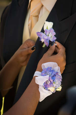 pinning: African teenaged girl fastening boyfriends boutonniere