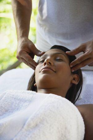 bathtowel: Hispanic woman receiving facial massage