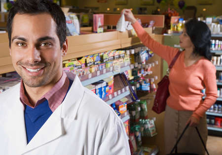 two visions: Pacific Islander pharmacist in front of customer LANG_EVOIMAGES