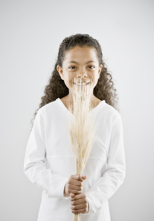 Mixed Race girl holding grain stalks